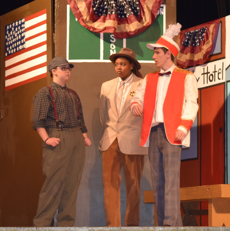 "Harold Hill (Clifford Farrington), right, meets with Constable Locke (Kimberlee Johnson), center, and Tommy Dijas (Molly Hulse) in a scene from Sterling High School's production of ""The Music Man."""