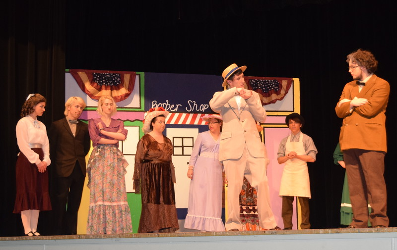 "Harold Hill (Clifford Farrington) talks with Ewart Dunlop (Chris Scott) as townspeople look on in a scene from Sterling High School's production of ""The Music Man."""