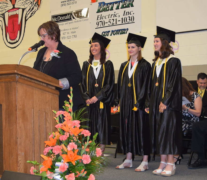 Jodene Boerner, assistant principal of Sterling High School, recognizes graduates who maintained a 4.0 grade point average throughout high school during the school's commencement exercises Saturday, May 28, 2016. From left; Lauren Szabo, Jenna Knudson and Cayla Carey.