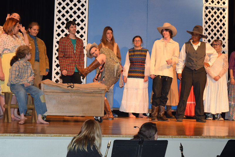 """Annie Oakley (Kori Penfold) performs a trick shot, as the crowd watches, during an audition for Buffalo Bill Cody's Wild West Show, in a scene from Sterling High School's upcoming production of """"Annie Get Your Gun."""""""