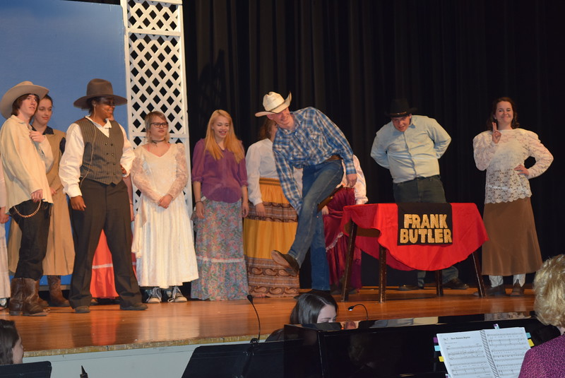 "The crowd watches as Frank Butler (Tyler Parks) shoots a trick shot at an audition for Buffalo Bill Cody's Wild West Show in a scene from Sterling High School's upcoming production of ""Annie Get Your Gun."""