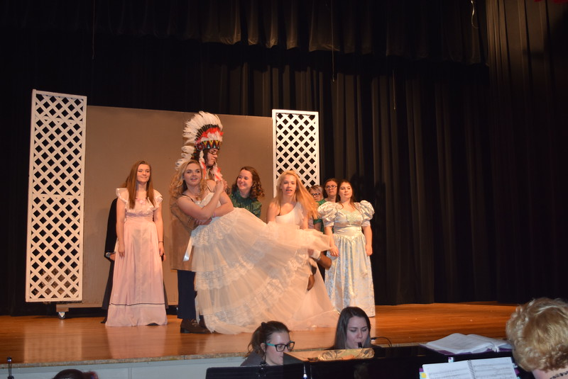 "Chief Sitting Bull (Gabriel DeLeon) helps Dolly Tate (Grace Reeves) and a debutant spin Annie Oakley (Kori Penfold) around, as other debutants look on, in a scene from Sterling High School's upcoming production of ""Annie Get Your Gun."""