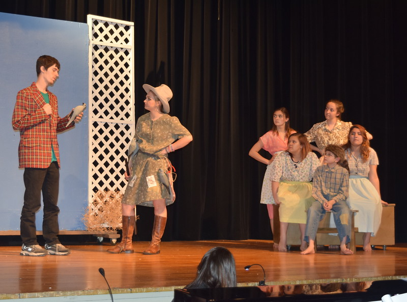 "Annie Oakley (Kori Penfold) presents a bird kill to Foster Wilson (Michael Kenner) in a scene from Sterling High School's upcoming production of ""Annie Get Your Gun."" Looking on are Annie's sisters and brother, from row, from left; Dessie (Destiny Boden), Little Jake (Roland Strobel), Kimmie (Kimberly Morales), back row, from left, Nellie (Jaden Penfold) and Jessie (Madison Trahern)."