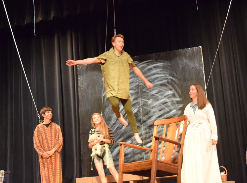"Peter Pan (Scott Glissmann) shows the Darling children – Wendy (Madison Trahern), John (Tristan Trahern) and Michael (Grace Graham) – how to fly in a scene from Sterling Miracle Players' upcoming production of ""Peter Pan."""