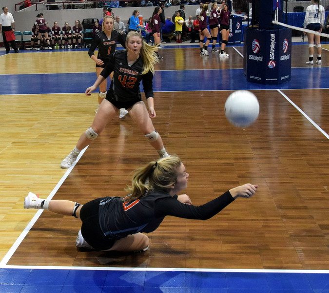 Ashlynn Berg dives to keep a ball in playing during the Tigers first game of the 3A state tournament at the Denver Coliseum.