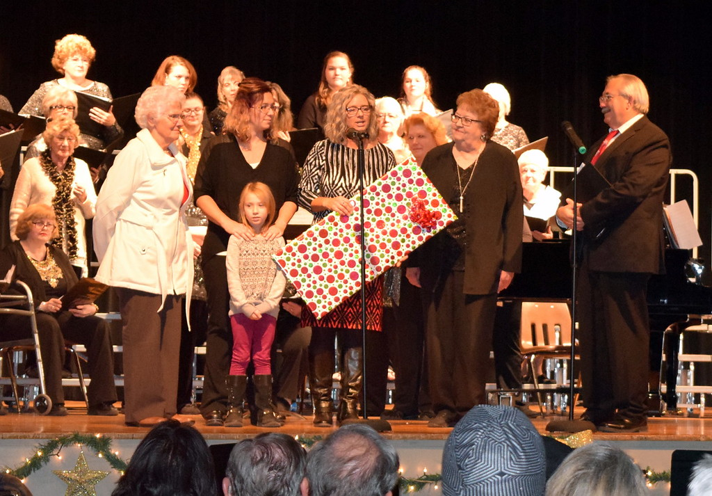 """. Windsong Chorus member Colleen Gardner, second from right, and Centennial State Chorus member Vic Wisdom present a cardboard check representing food and monetary donations collected at the group\'s \""""Christmas Celebration!\"""" concert Sunday, Dec. 3, 2017, to Richelle Greenwood, center, director of Cooperating Ministries of Logan County and her assistants. According to Greenwood, they provide services to an average of 250 to 260 families a month. Food collected at the concert will help the one in seven people in Logan County that suffer from some kind of food insecurity."""