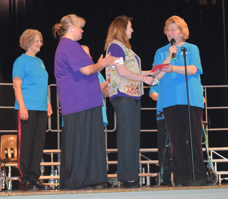 Windsong Chorus director Annette Lambrecht, right, and chorus members Ce Merrigan, left and Dana May, second from left, present chorus member April Martin with a Northeastern Junior College Book Award, to help her cover the costs of books at NJC, during the chorus' Barbershop Festival and Show Saturday, June 10, 2017.