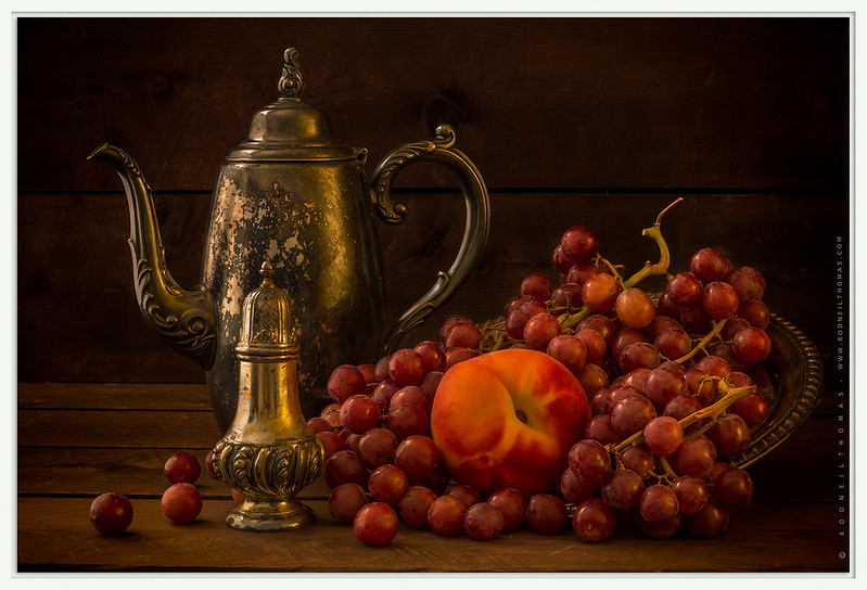 A still life setting consisting of fruit and a teapot.