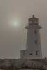 The lighthouse in Peggy's Cove is partially obscured by fog