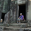 Senior man sitting at the doorway of temple, Siem Reap, Cambodia