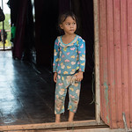 Girl standing at doorway of her house, Siem Reap, Cambodia
