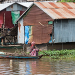 Woman sitting in rowboat moving in Tonle Sap lake, Kampong Phluk, Siem Reap, Cambodia