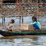 People sitting on rowboat in Tonle Sap lake, Kampong Phluk, Siem Reap, Cambodia