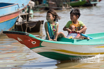 Children sitting in boat moving in Tonle Sap lake, Kampong Phluk, Siem Reap, Cambodia