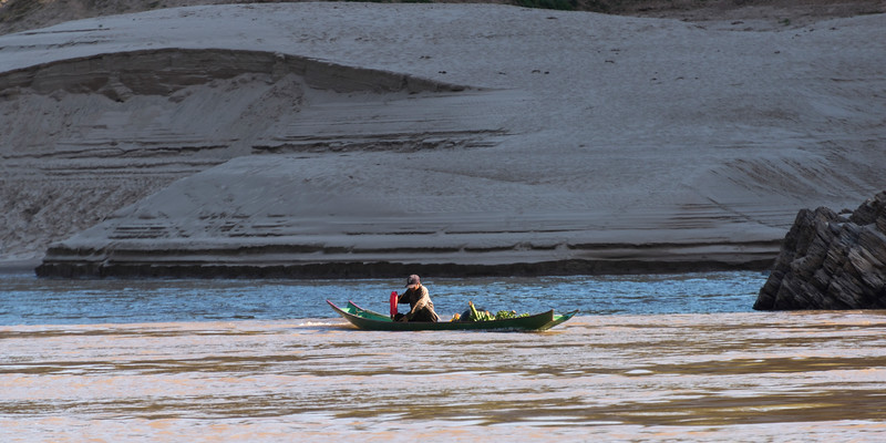 Man sitting on boat in River Mekong, Laos