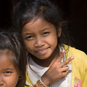 Portrait of two adolescent local girls gesturing, Ban Houy Phalam, Laos