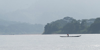 Fisherman with his net on boat in River Mekong, Laos