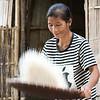 Woman tossing rice in basket, Ban Gnoyhai, Luang Prabang, Laos