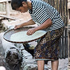 Woman winnowing rice in basket, Ban Gnoyhai, Luang Prabang, Laos