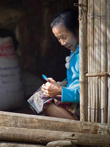 Senior woman cutting food with knife, Ban Gnoyhai, Luang Prabang, Laos