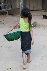 Rear view of girl carrying basket, Ban Gnoyhai, Luang Prabang, Laos