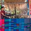Woman weaving shawls on loom, Laos
