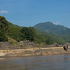 Scenic view of riverbank with mountain range in background, River Mekong, Sainyabuli Province, Laos