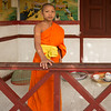 Portrait of boy monk standing by railing at temple, Luang Prabang, Laos