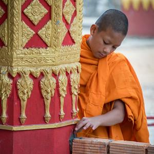Boy monk standing outside temple, Luang Prabang, Laos