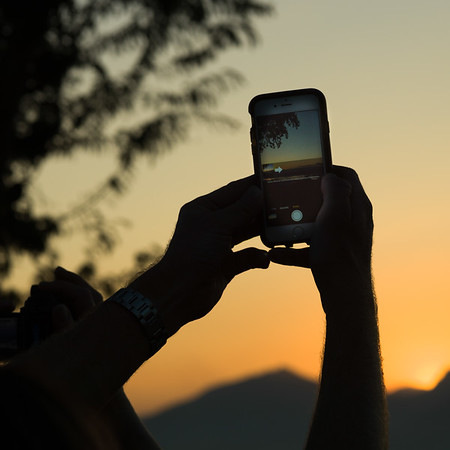 Person's hand taking picture with smartphone, Mount Phousi, Luang Prabang, Laos