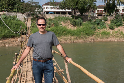 Man standing on bamboo bridge, Nam Khan river, Luang Prabang, Laos