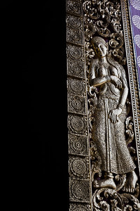 Female sculpture carved on door of temple, Wat Xieng Thong, Luang Prabang, Laos