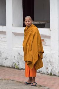 Portrait of boy monk standing outside temple, Luang Prabang, Laos