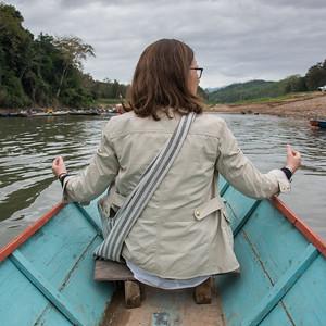 Woman sitting on boat in Nam Khan river, Luang Prabang, Laos