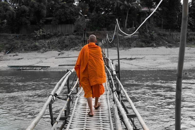 Monk walking on bamboo bridge over Nam Khan river, Luang Prabang, Laos