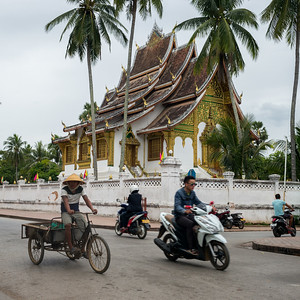 People riding vehicles on road with Royal Temple in background, Haw Pha Bang, Luang Prabang, Laos