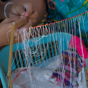 Person's hands weaving craft product