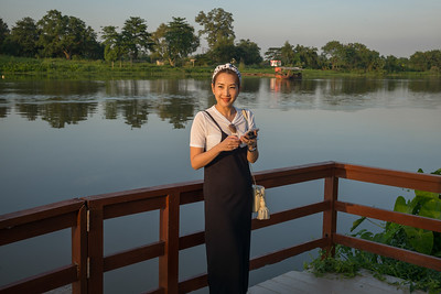 Happy woman standing at lakeside, Chiang Rai, Thailand