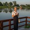 Happy woman standing at lakeside, Chiang Rai, Thailand