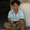 Portrait of happy woman sitting at doorstep, Chiang Rai, Thailand