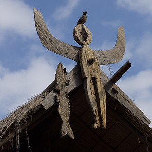 Low angle view of bird perching on sculpture, Chiang Rai, Thailand