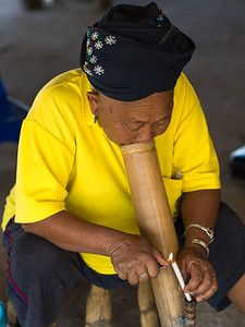 Elderly woman lighting a cigarette, Chiang Rai, Thailand