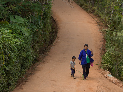 Elevated view of woman walking with her son on road, Chiang Rai, Thailand