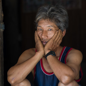 Portrait of man sitting with face in hands, Chiang Rai, Thailand