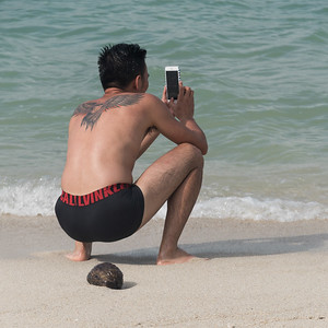 Tourist taking picture with mobile phone on beach, Koh Samui, Surat Thani Province, Thailand