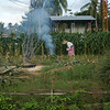 Woman burning leaves in field, Koh Samui, Surat Thani Province, Thailand