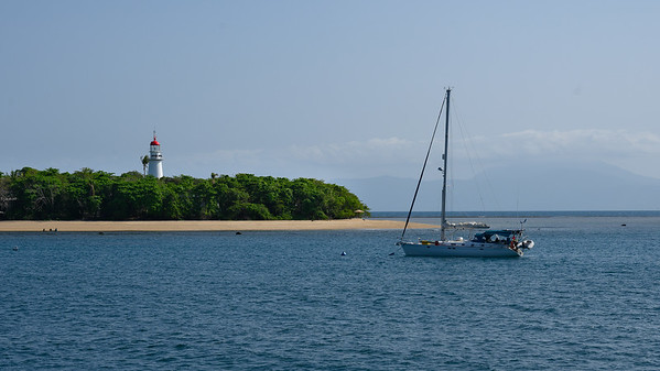 Boat in the ocean with lighthouse in the background, Port Douglas, Queensland, Australia