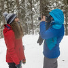 Tourists taking a picture in snow covered forest, Johnston Canyon, Banff National Park, Alberta, Canada