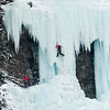 Ice climber ascending frozen waterfall, Banff National Park, Alberta, Canada
