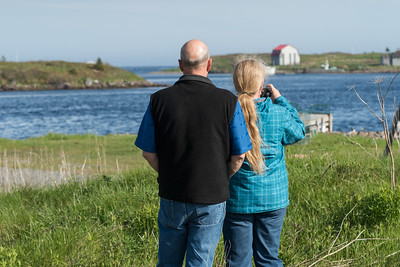 Rear view of couple taking picture with camera at riverbank, Cape Breton Island, Nova Scotia, Canada